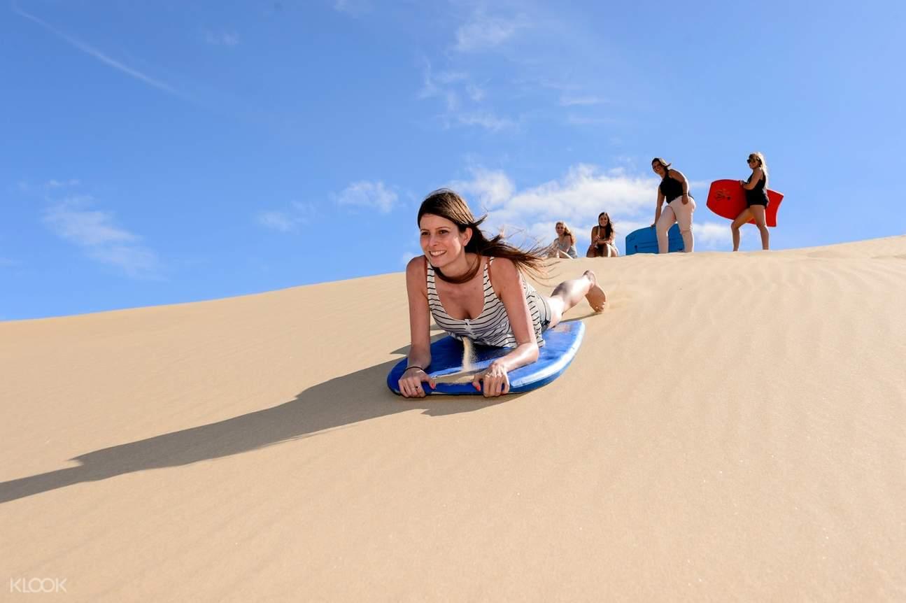 girl going sand boarding on ninety mile beach