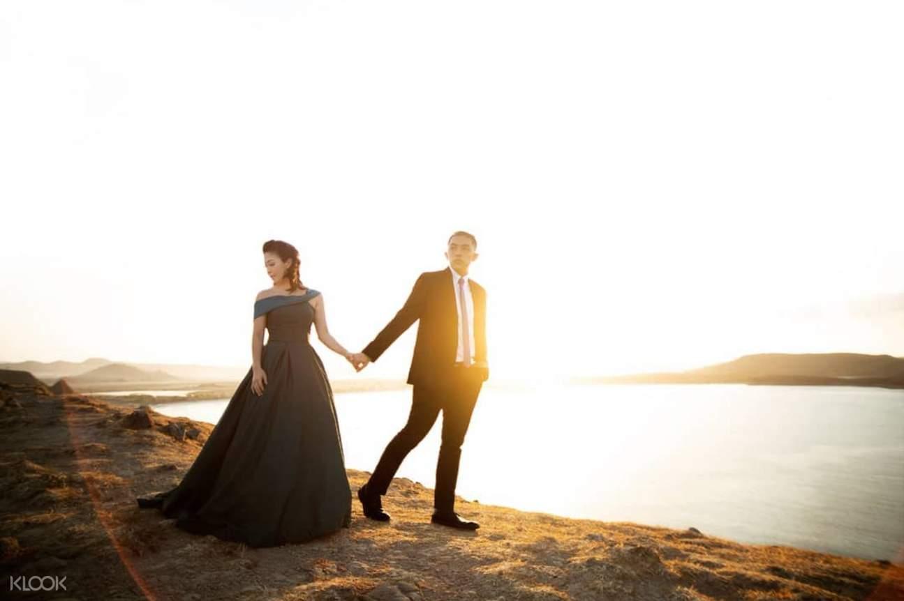 Man and woman walking next to lake