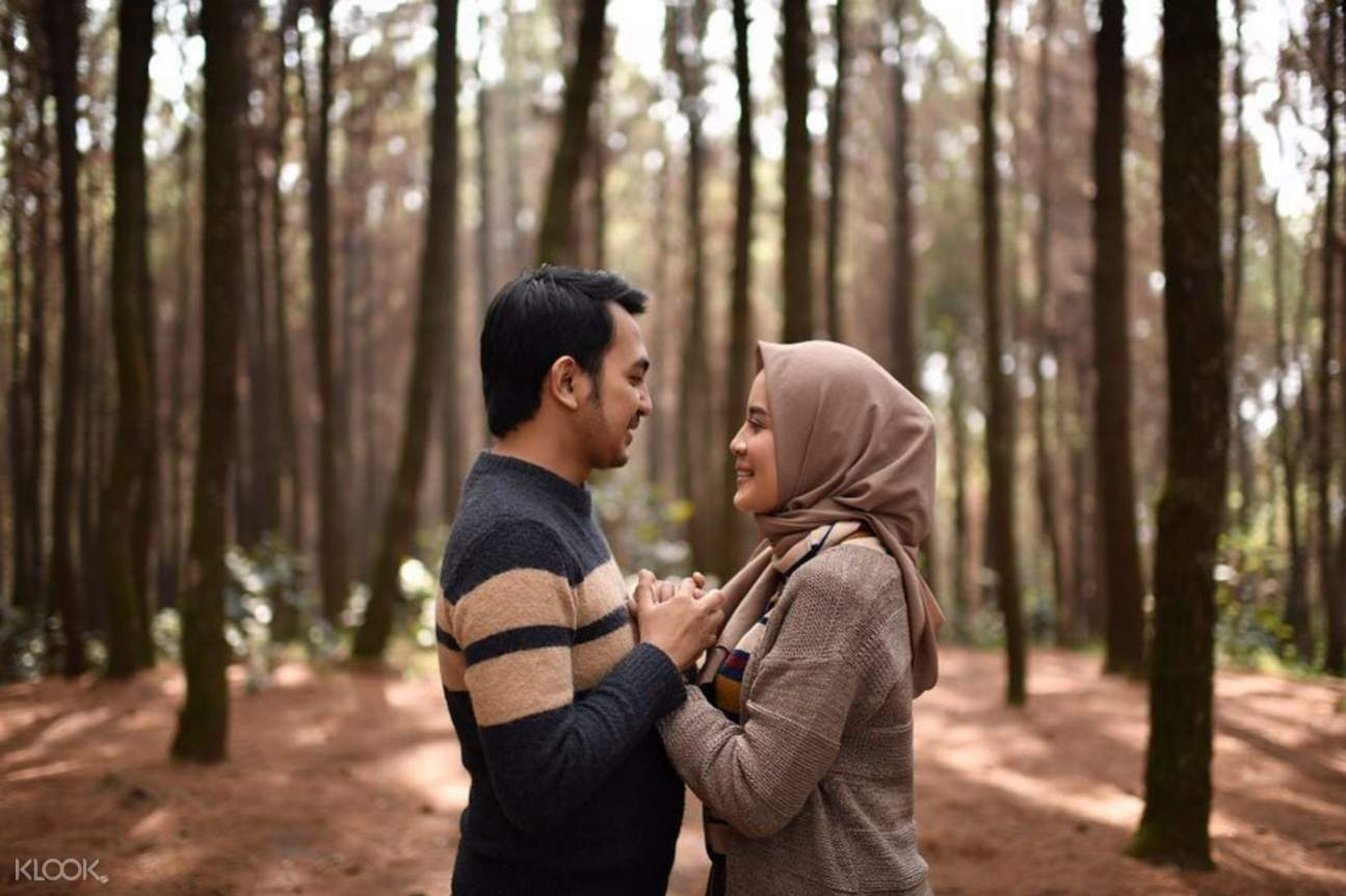 Man and woman holding hands in a forest