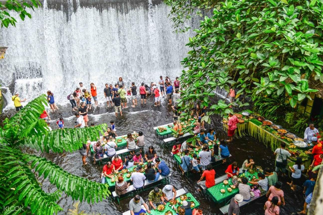 manmade waterfall with swarm of tourists