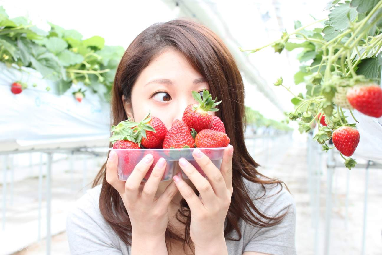 woman holding a tray of strawberries at ichigo world