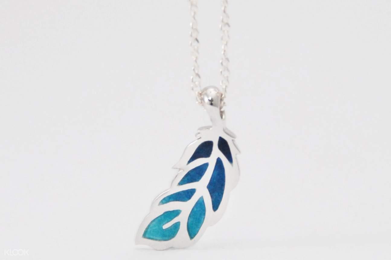 彩羽項鍊透過高溫窯燒手工製作完成,將琺瑯釉料豐富多彩的顏色呈現於金屬之上