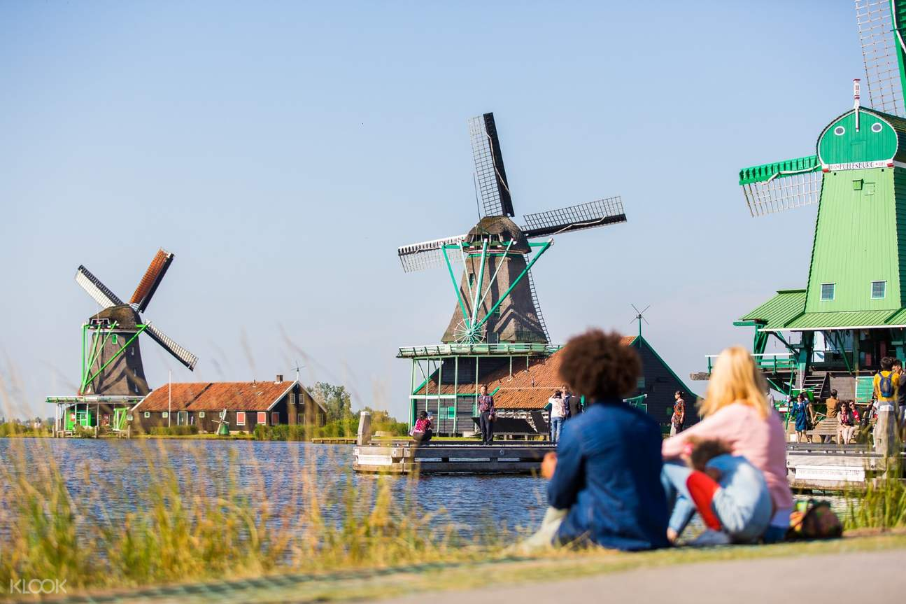 couple looking at a windmill beside the river