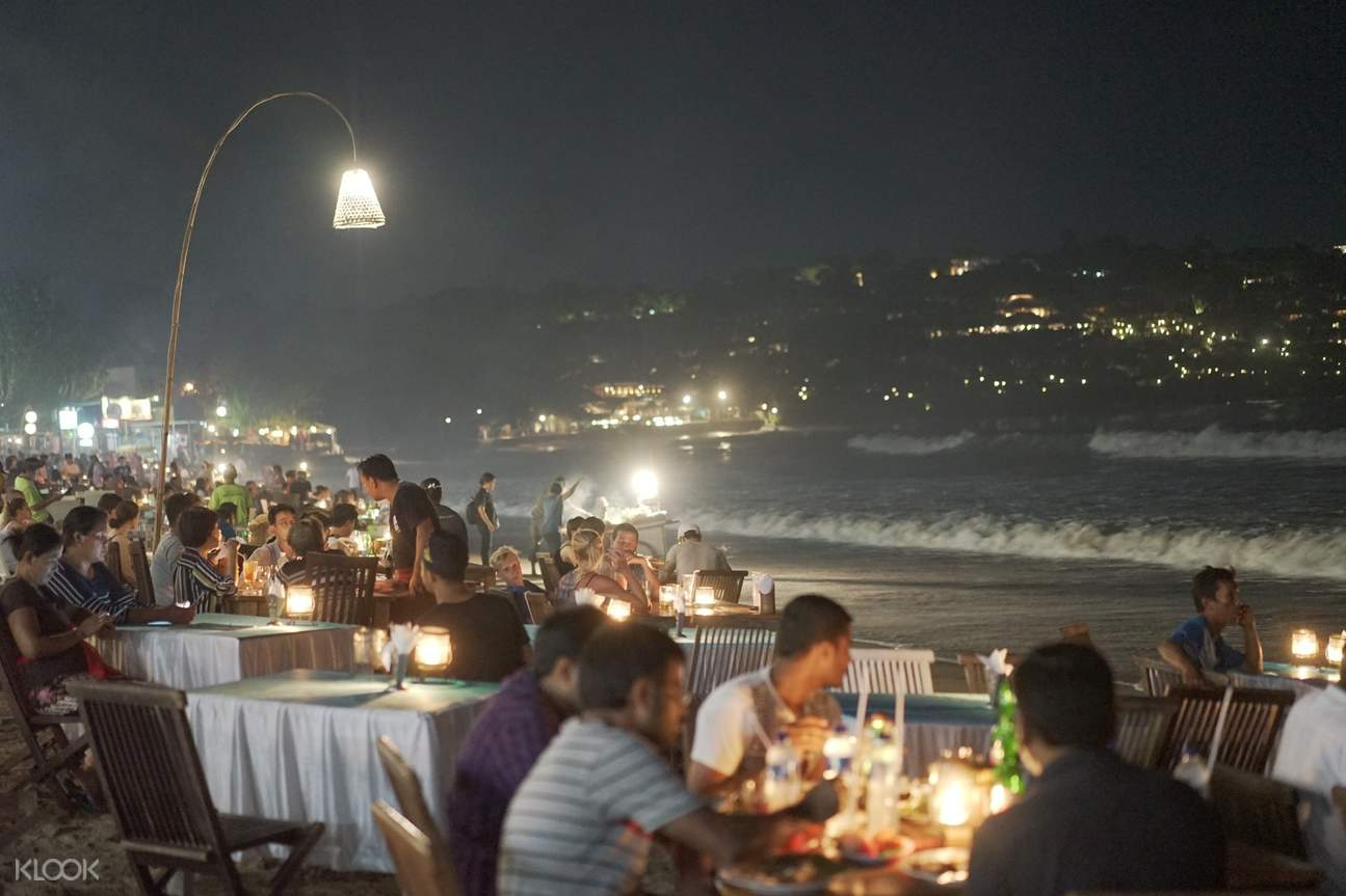 people have dinner by the seaside