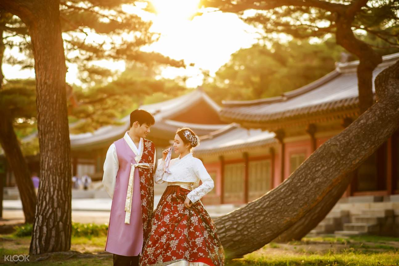 a couple wearing hanboks standing in front of a tree