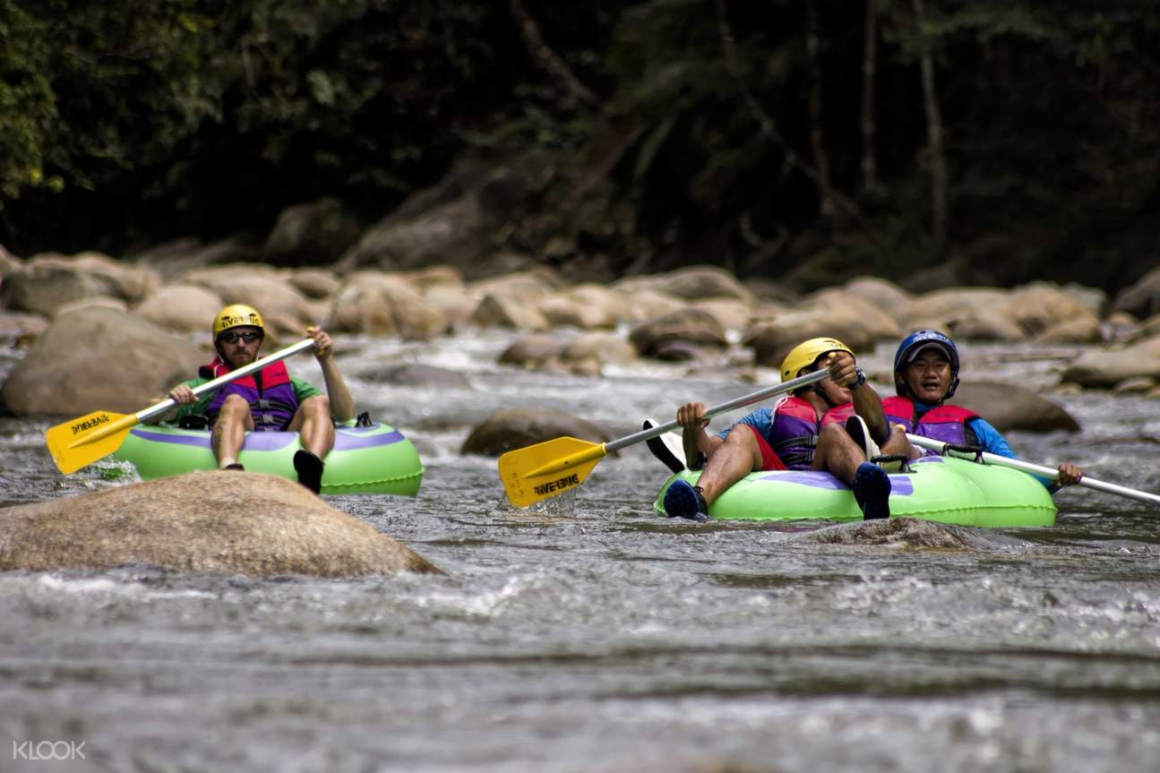 group of guys river tubing in gopeng river