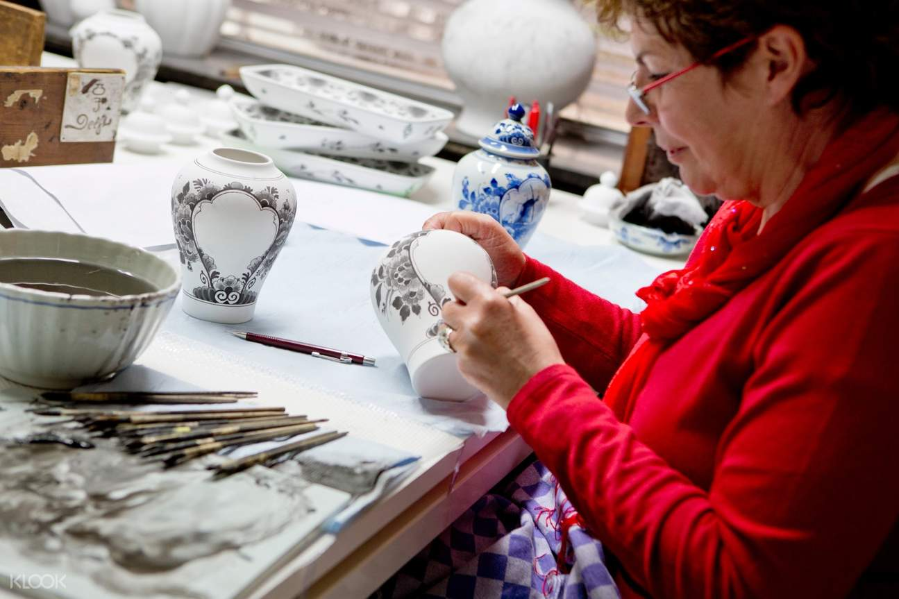 artist painting on pieces of earthenware by delft blue