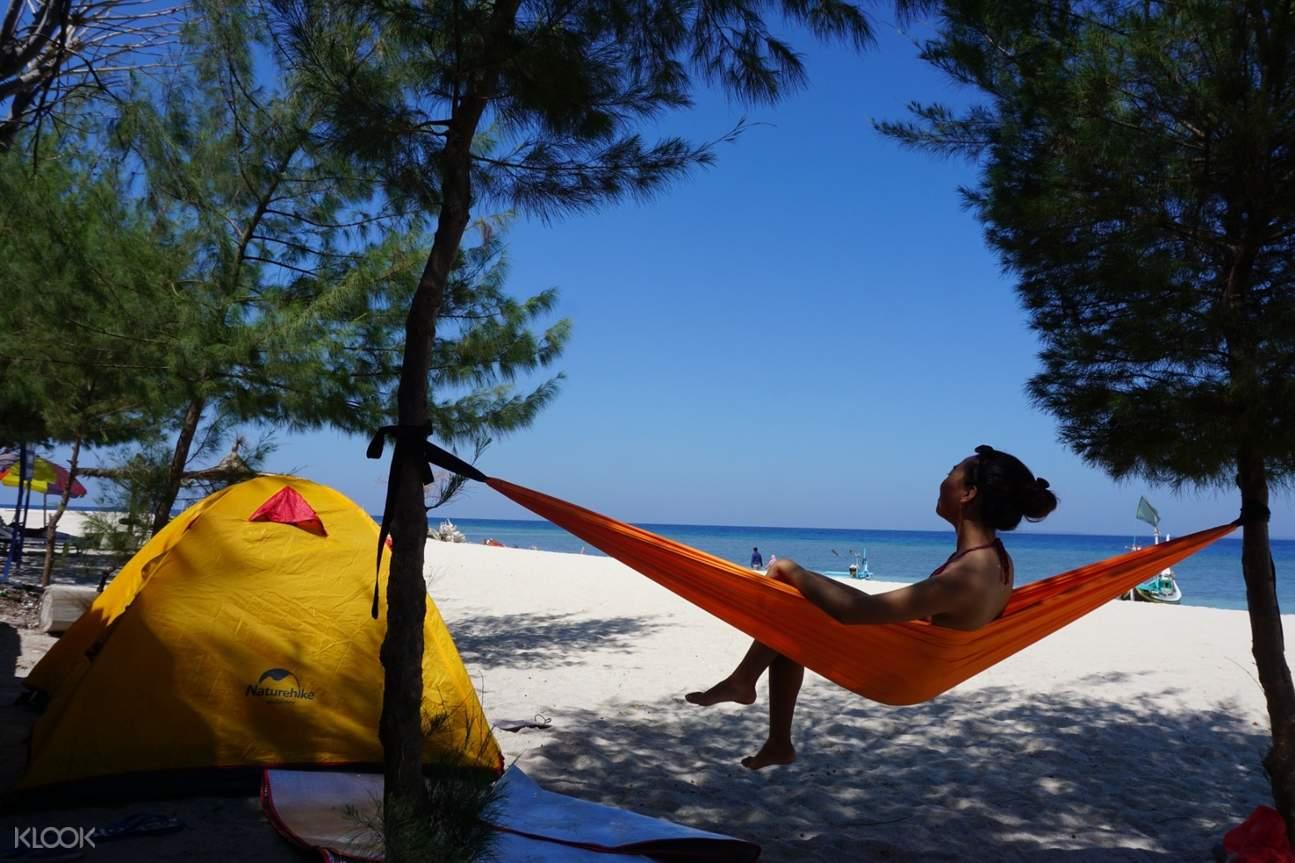 perempuan di atas hammock tepi pantai