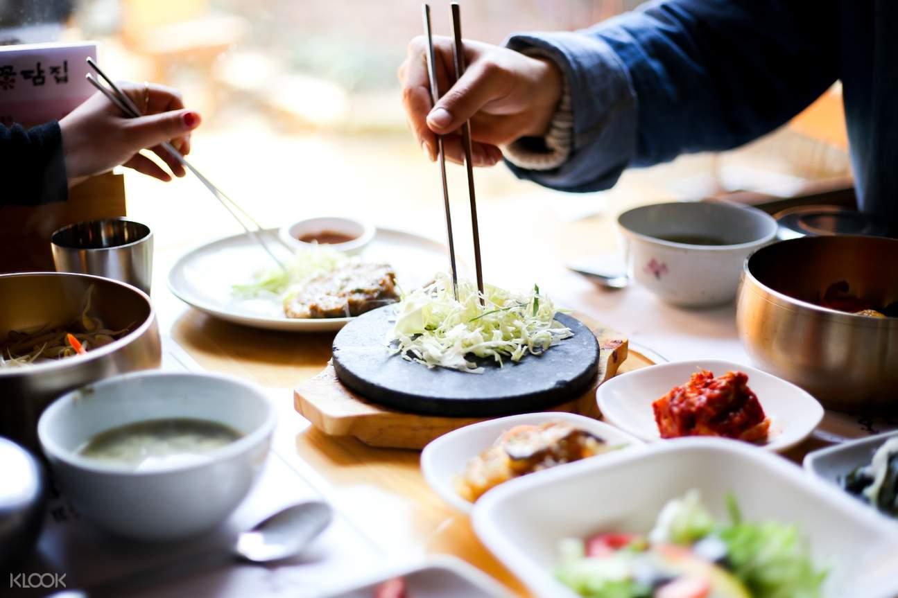 people getting korean cuisines with chopsticks