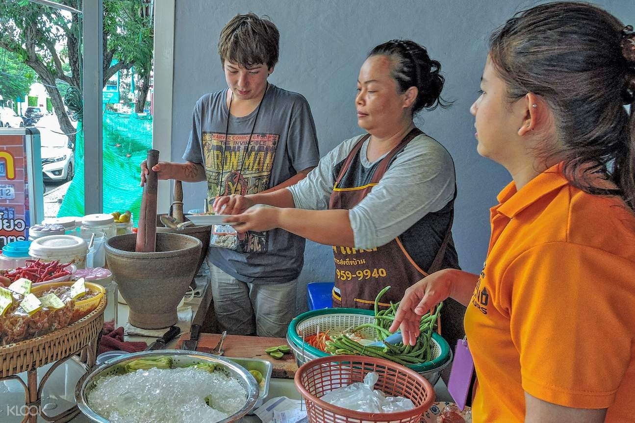thai locals offering local food to tourists