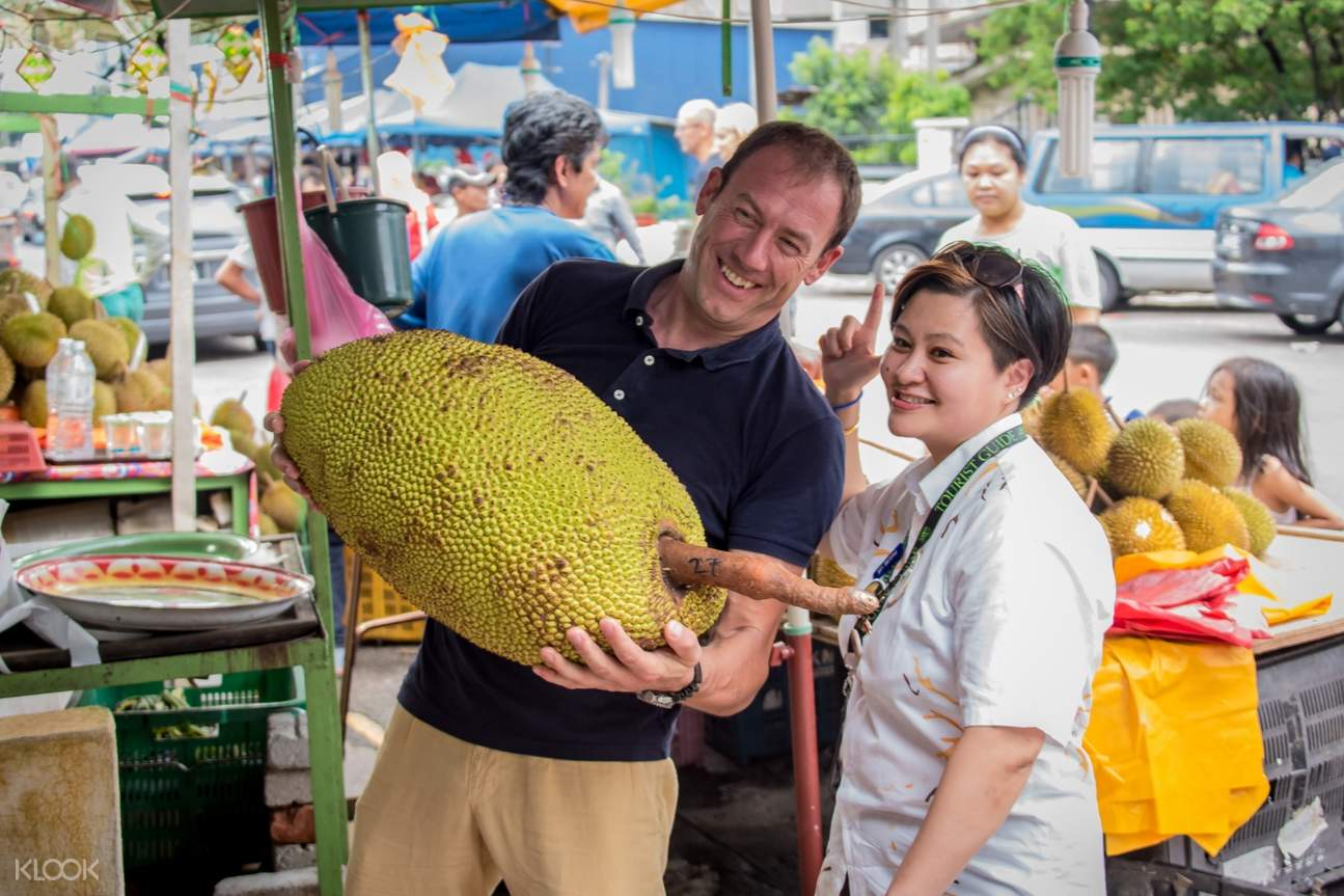man holding durian with a woman