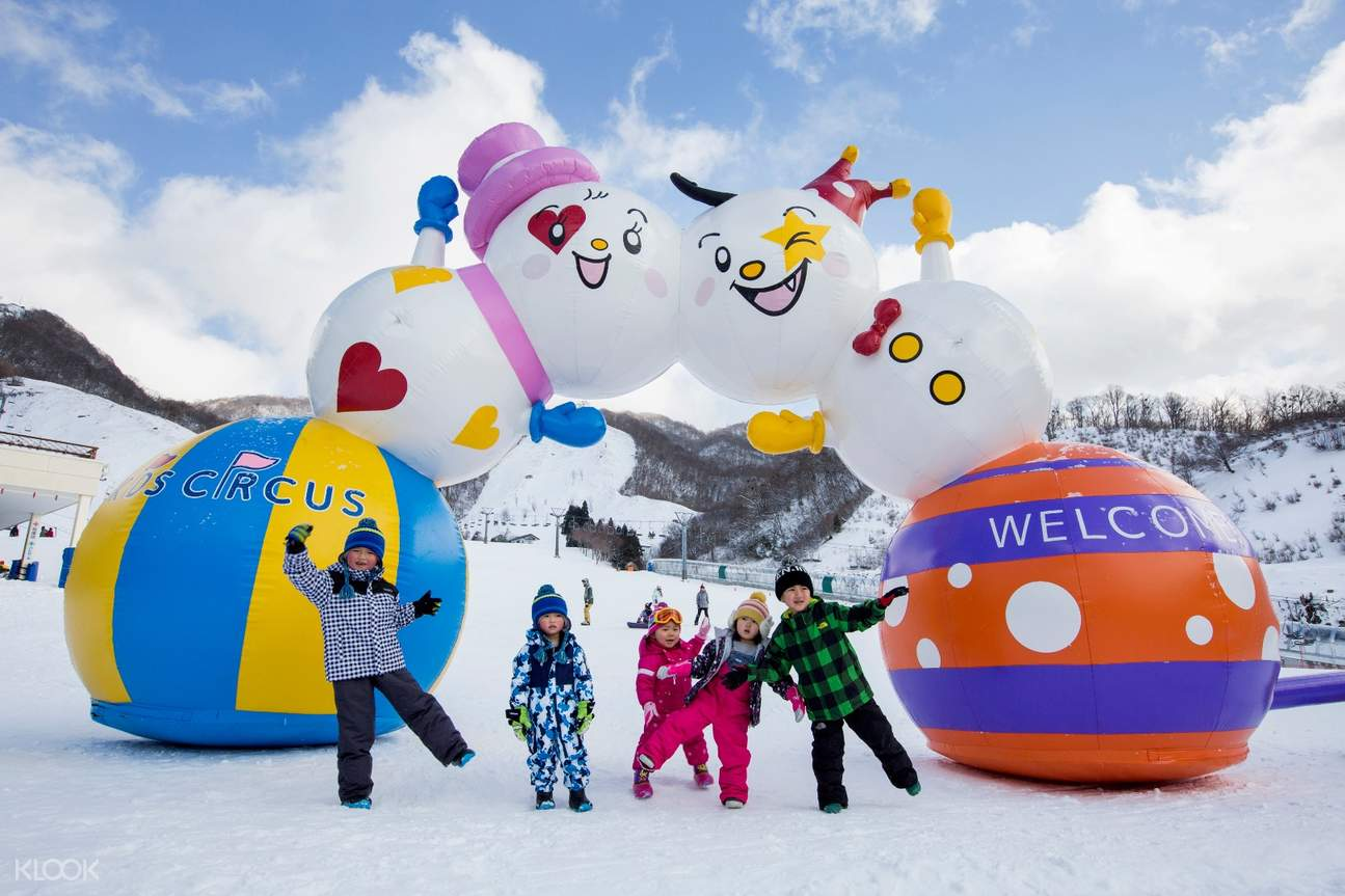 group of children posing in front of snow resort welcome sign