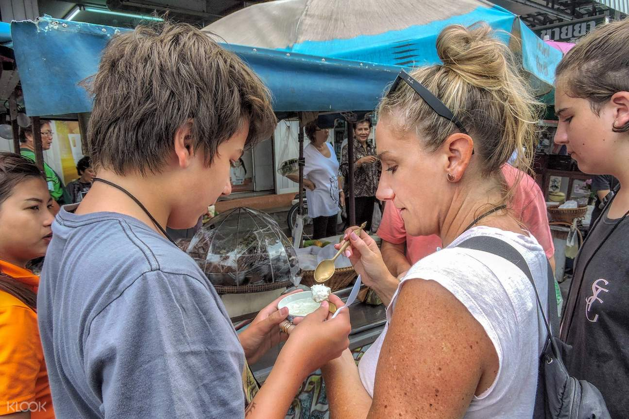 tourists tasting local thai food