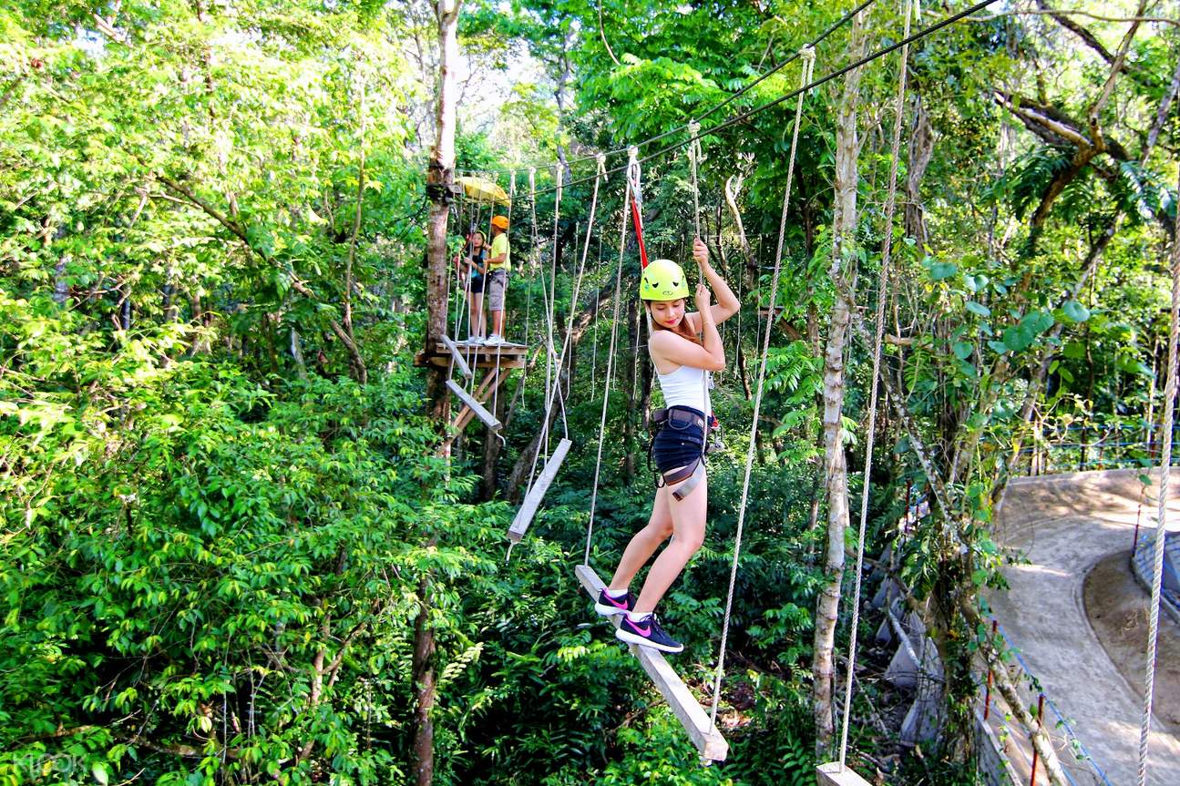 a woman holding on a rope course