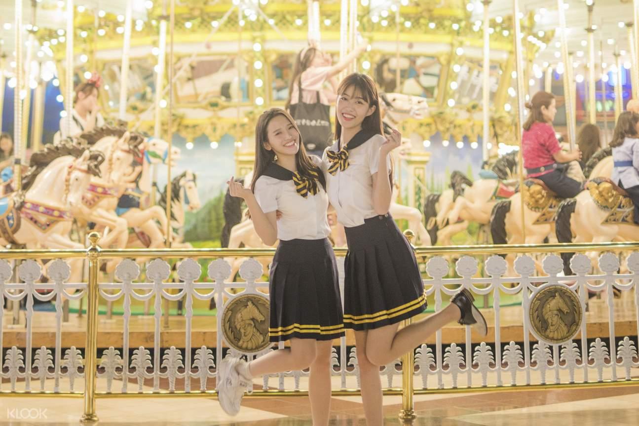 two women wearing korean school uniform at a theme park