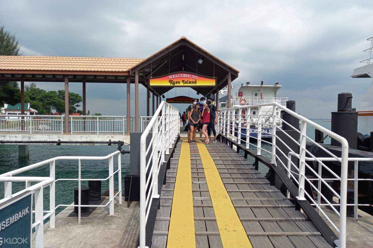 Friends are taking picture in front of the Kusu Island's signboard