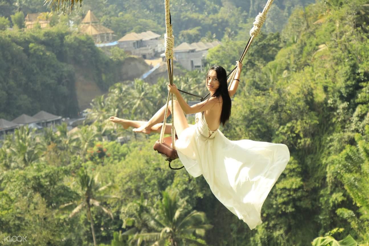 woman on bali swing rock