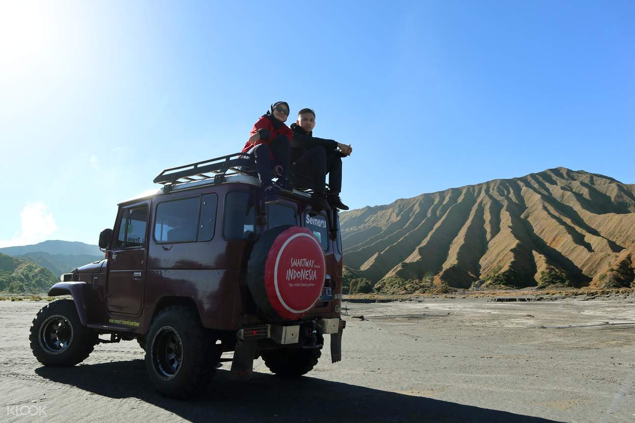 two people beside a jeep somewhere in the black sand desert near Mount Bromo