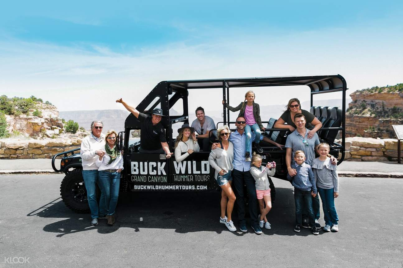 a hummer with passengers posing for a photo near the Grand Canyon