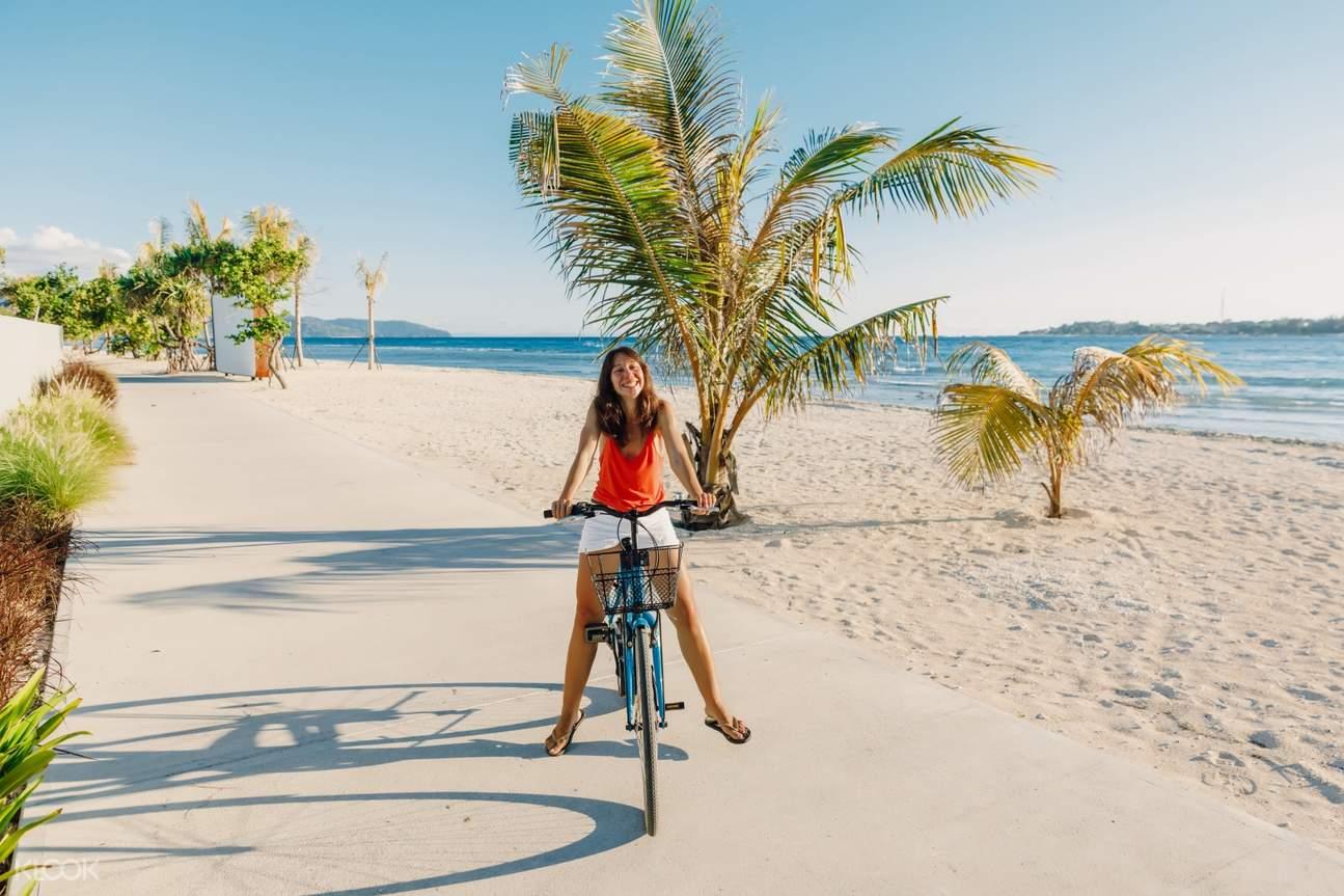 woman biking at the beach in gili trawangan