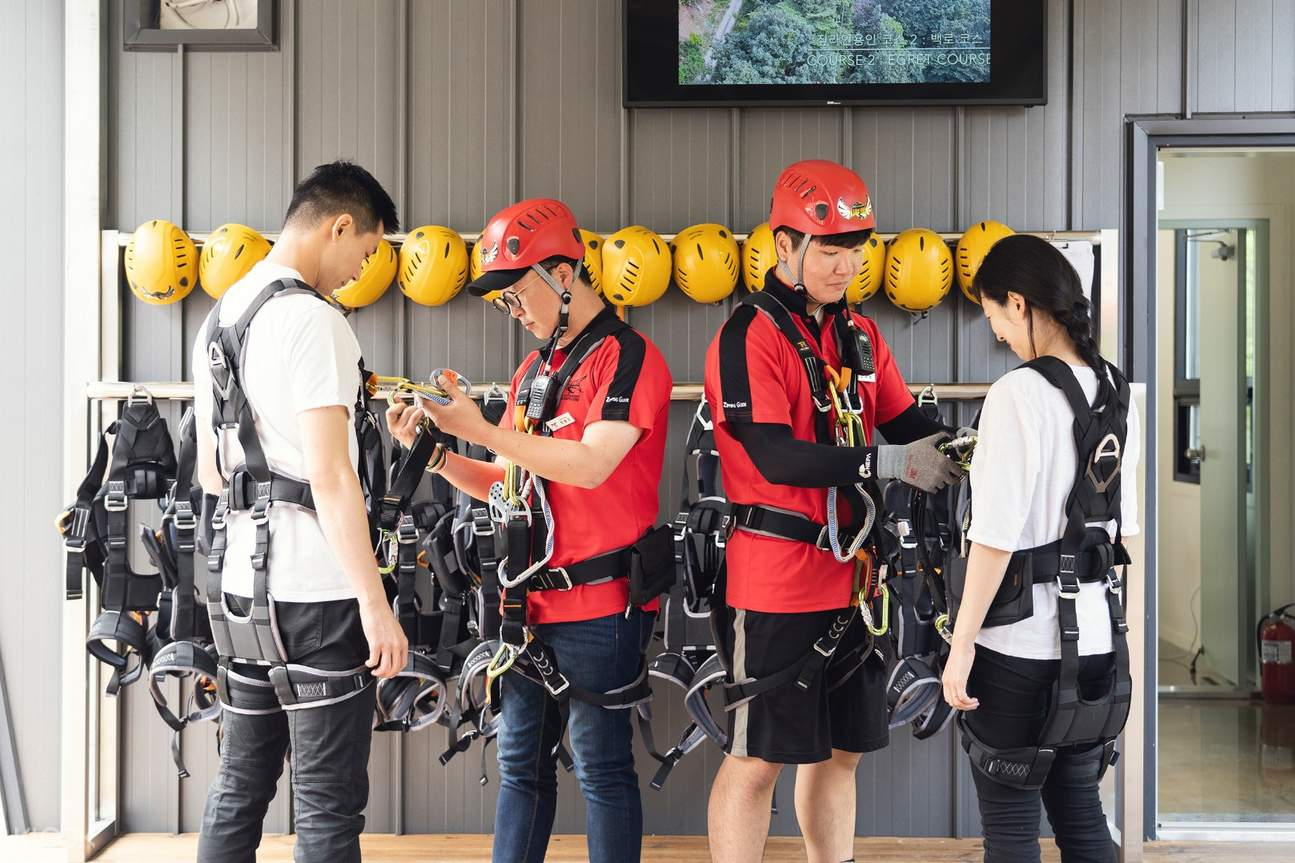 guides strapping safety gears to guests