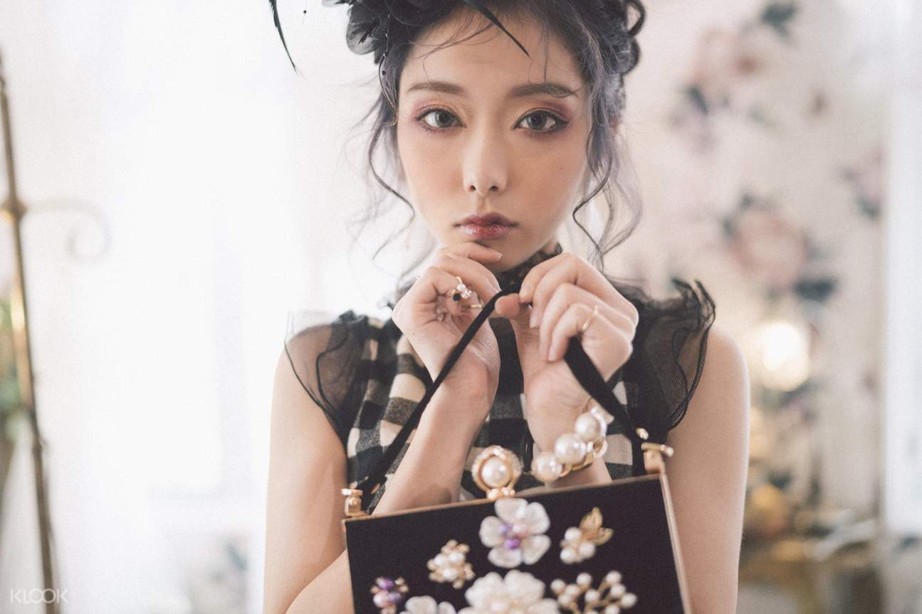 a girl is taking picture with the handbag and flowers around