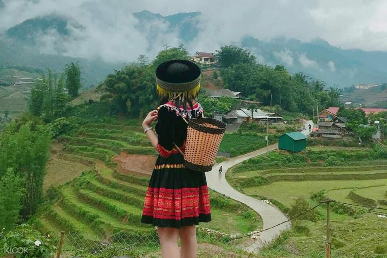 Woman posing with her back and a backdrop of rice terraces in Sapa