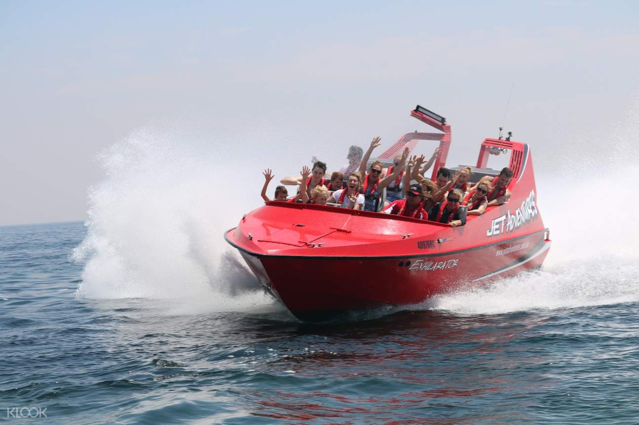 tourists on jet boat with hands up