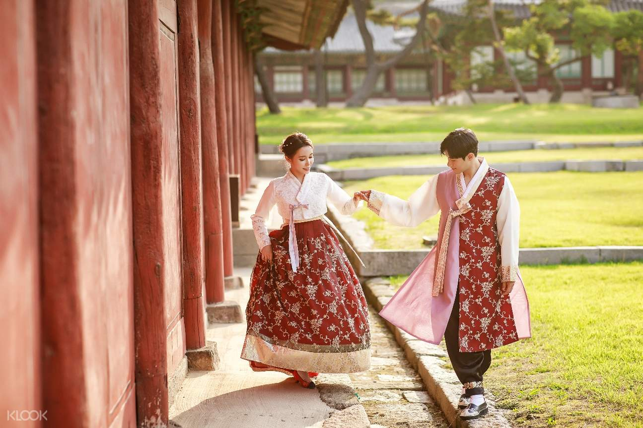 a couple wearing hanboks strolling beside a wall