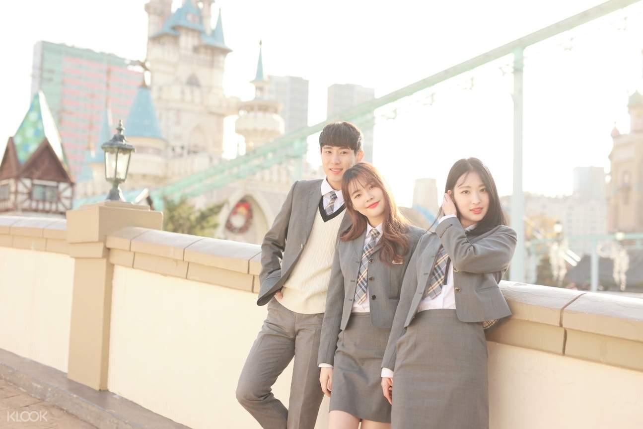 group of friends wearing korean school uniform at a theme park