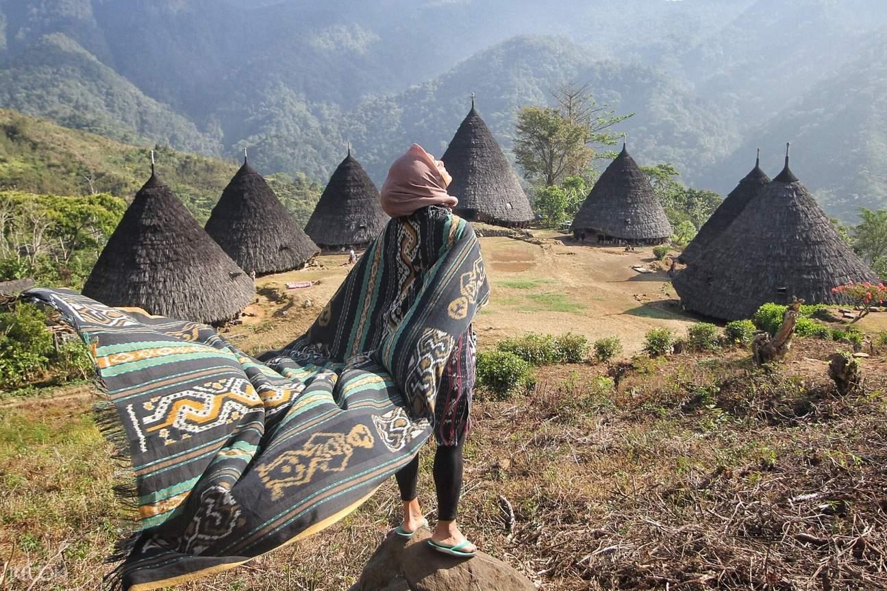 girl in traditional cone shape huts in wae rebo