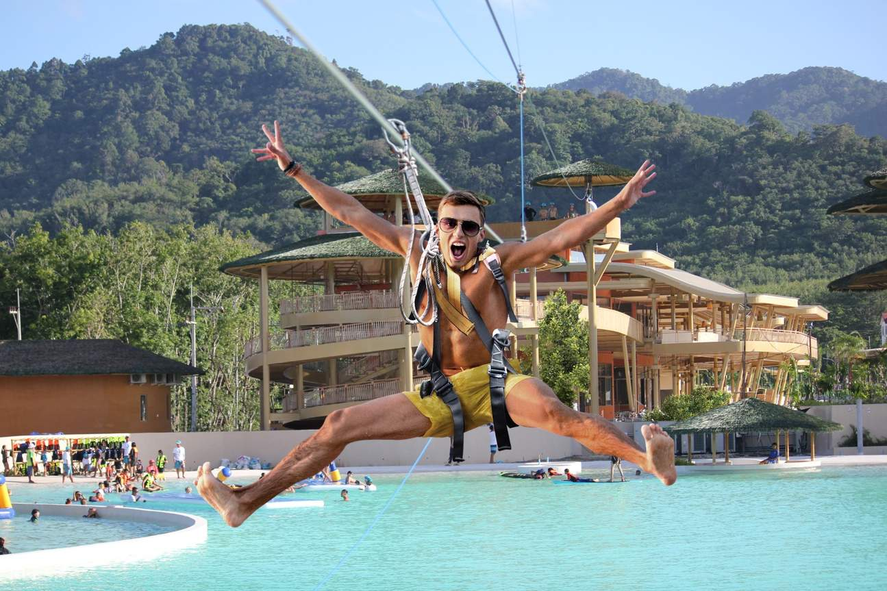 man on zipline above swimming pool