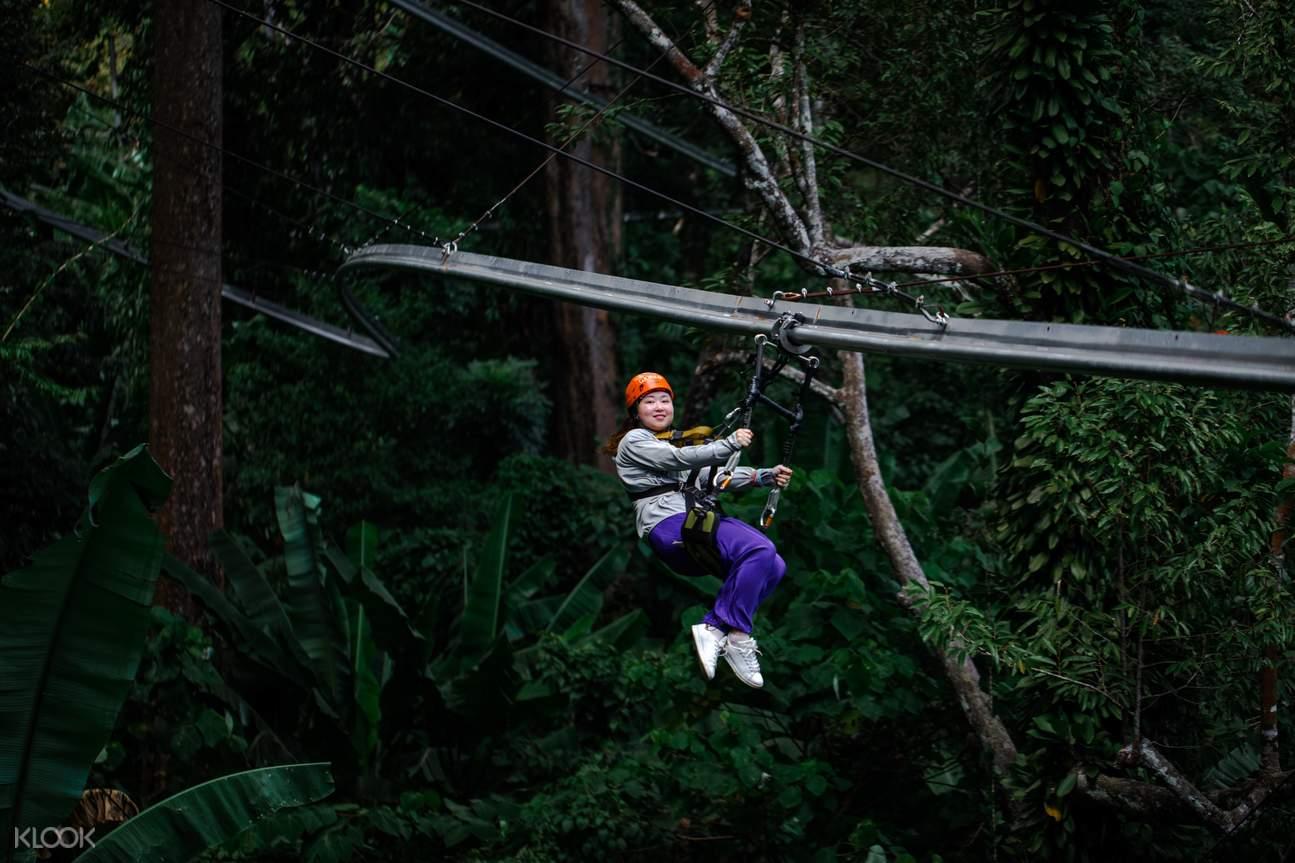 tourist swinging through the jungle at zipline park in Phuket
