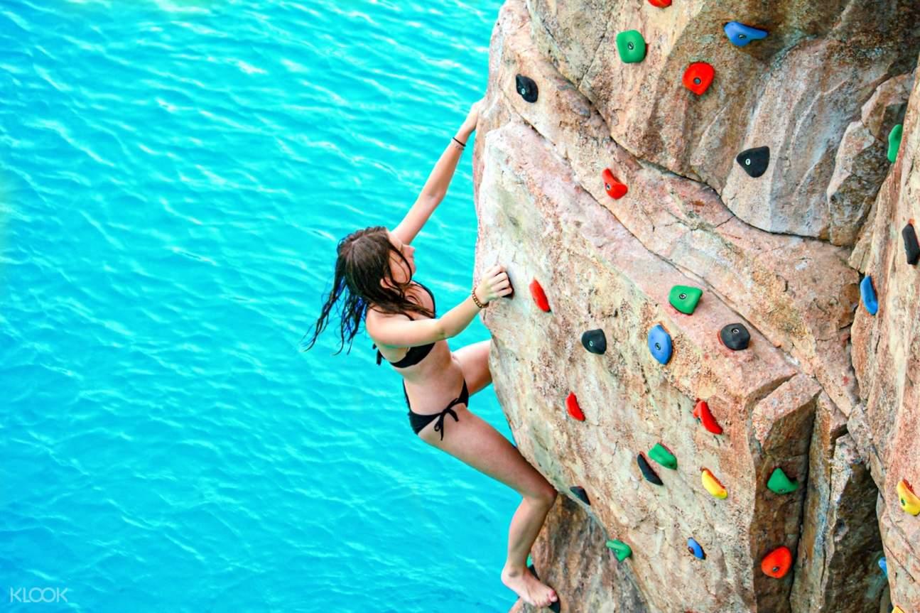 woman rock climbing above a swimming pool