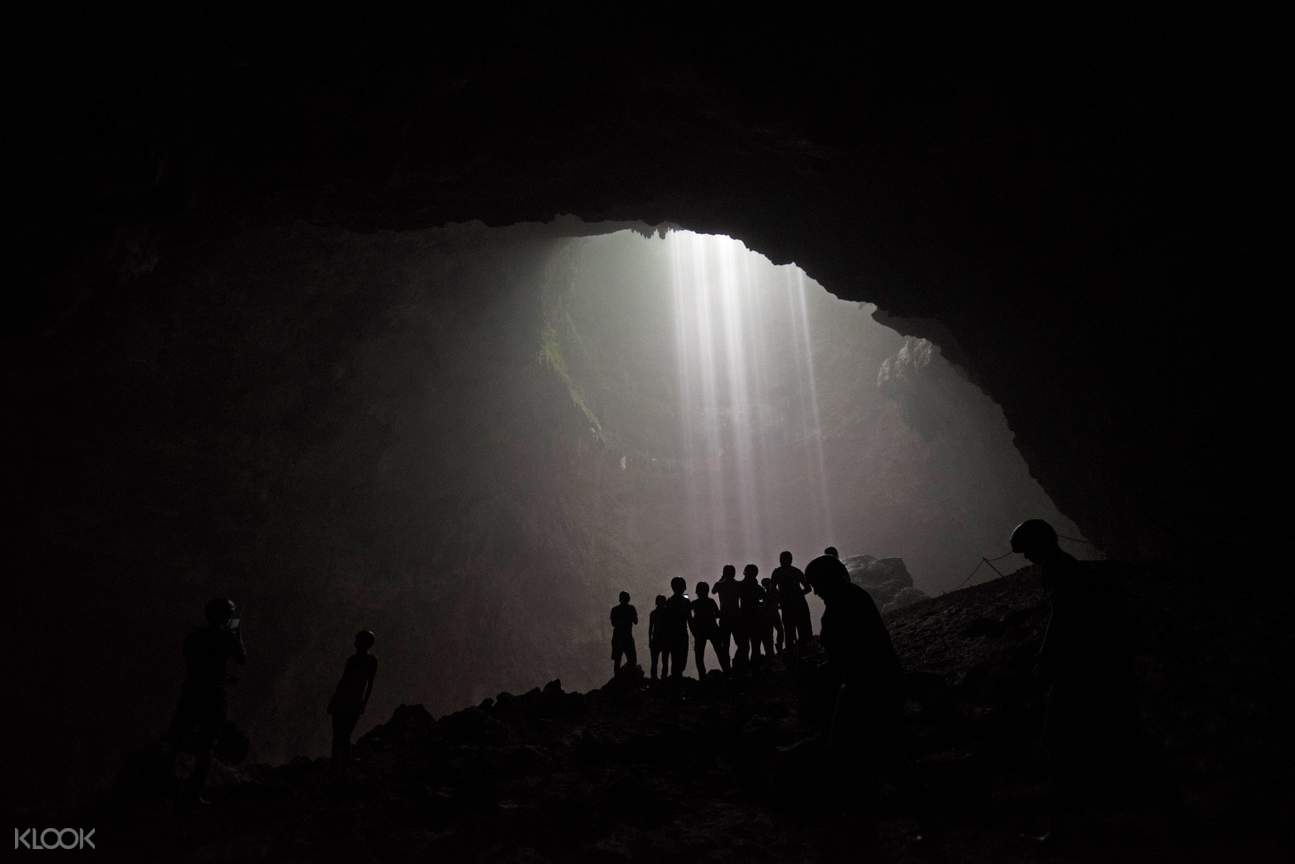 silhouette of tourists posing inside jomblang cave