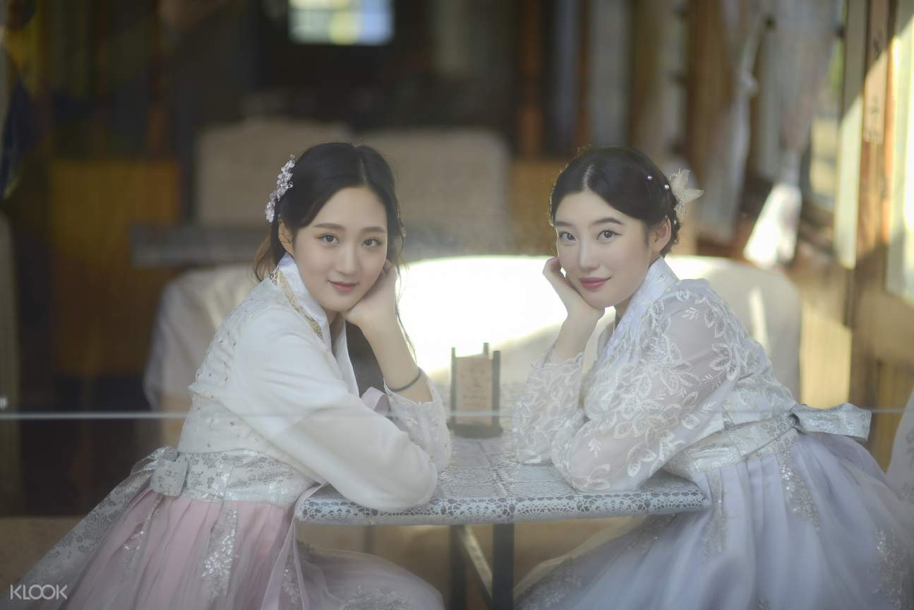 two girls in hanbok sitting on a table