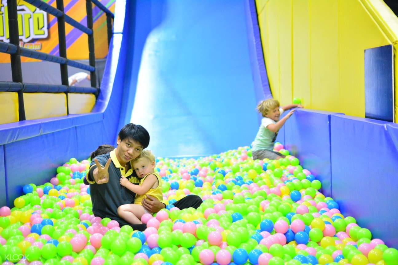 kids and adult in ball pit at the bottom of a slide