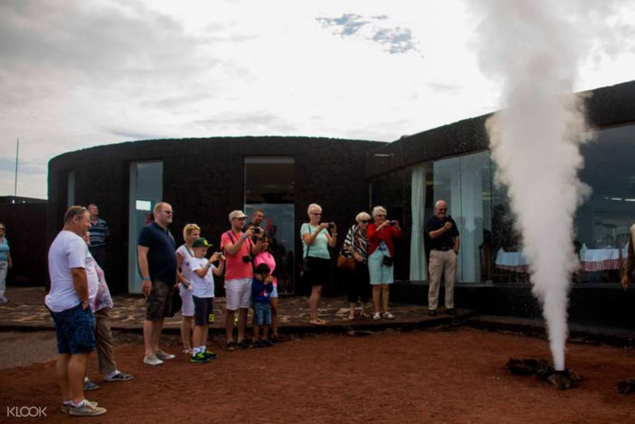tour group looking at smoke in monta?as del fuego timanfaya