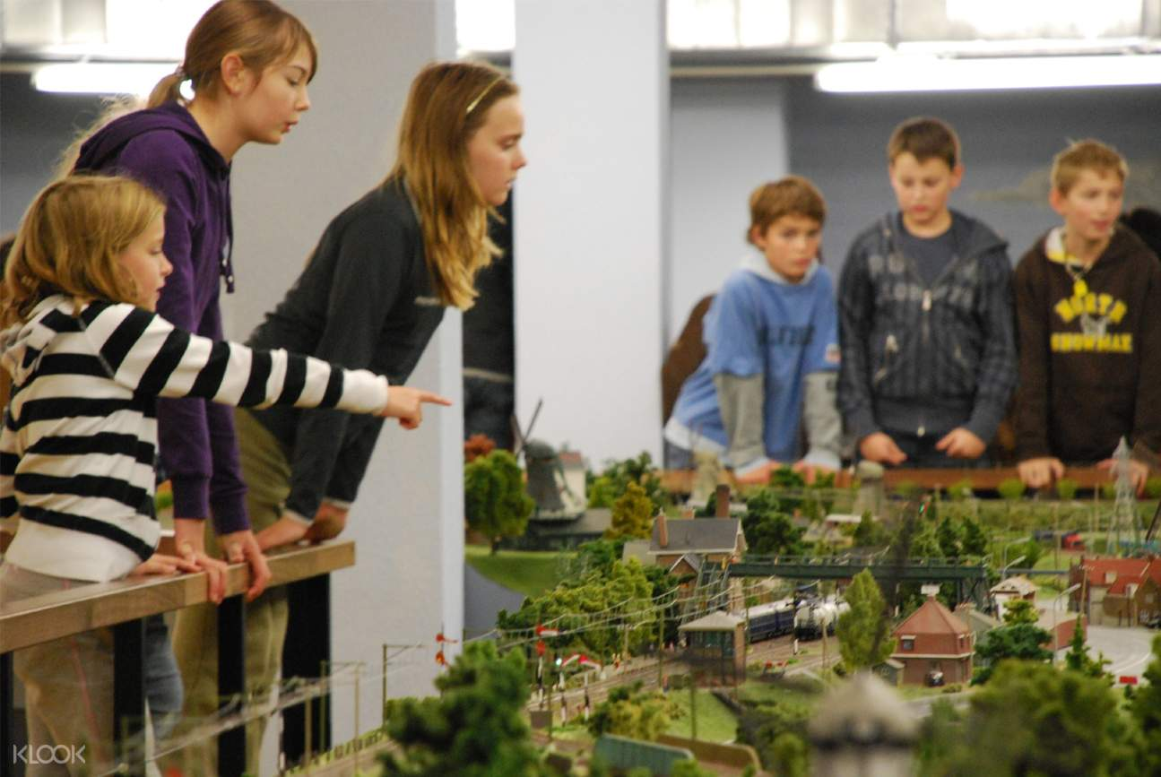kids pointing and watching the miniature world simulations