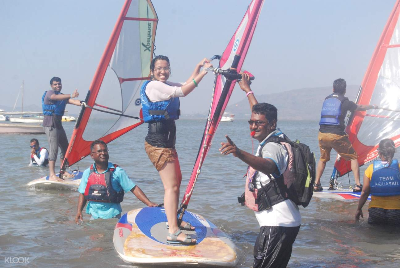 tourists pose for a photograph before windsurfing