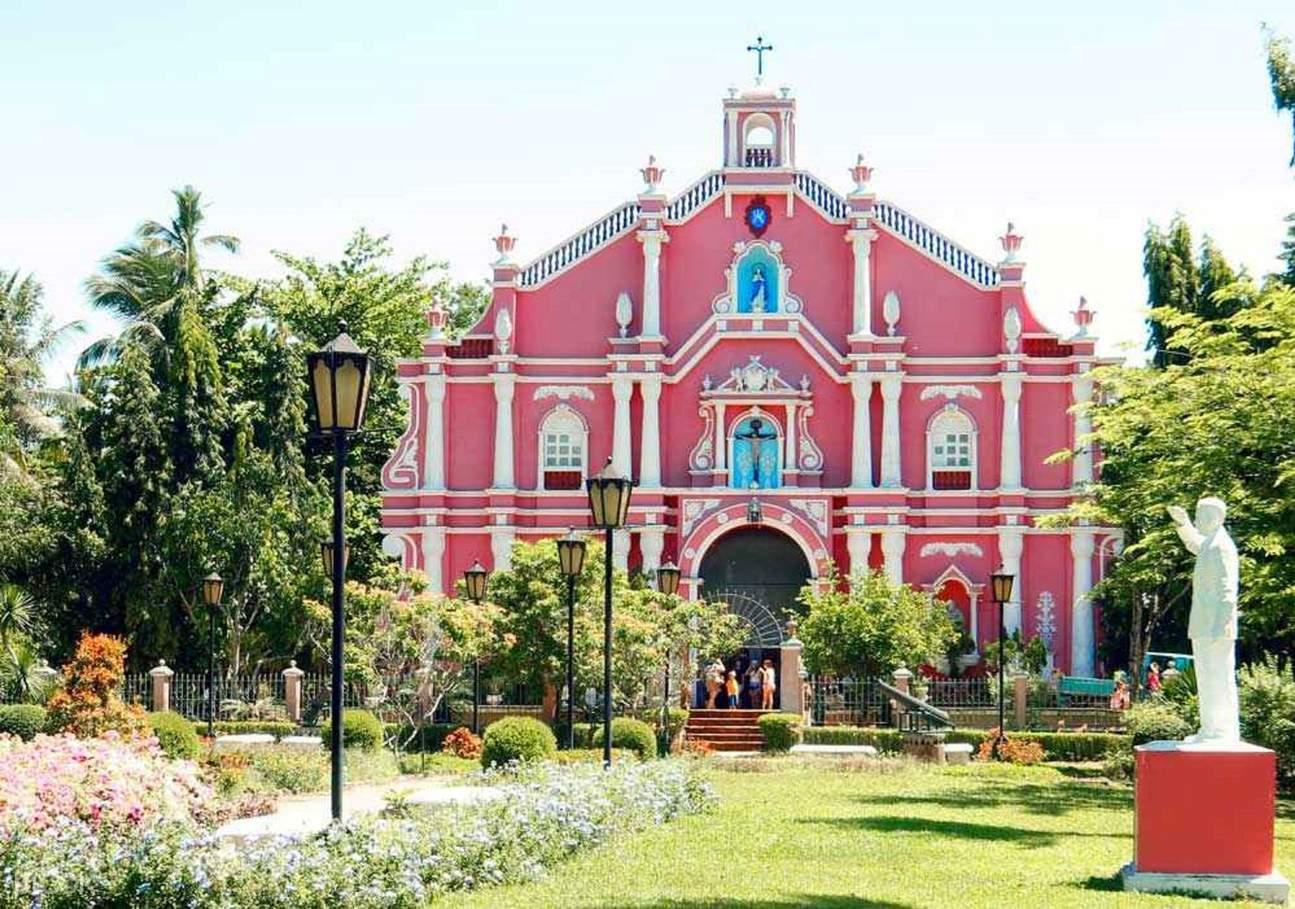 facade of a pink church in villa escudero