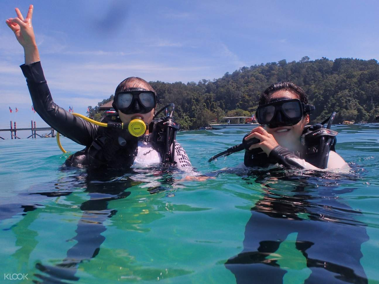 two persons scuba diving in gaya island