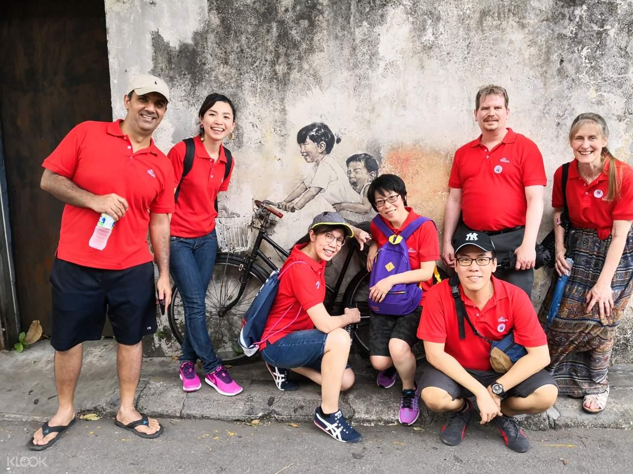 people posing in front of a street mural in penang