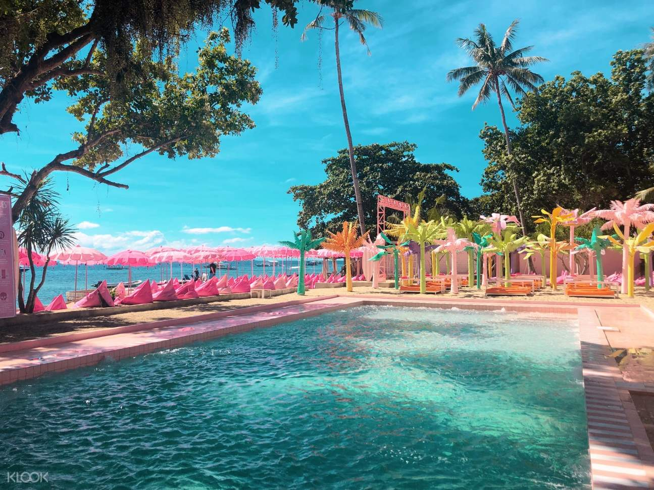 the pink pool with artificial rainbow colored trees and pink loungers surrounding it