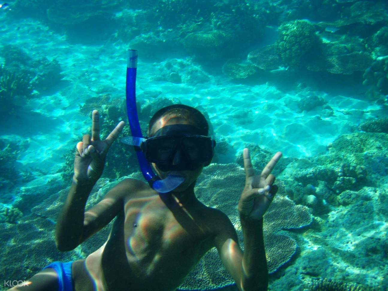 kid poses for an underwater photograph
