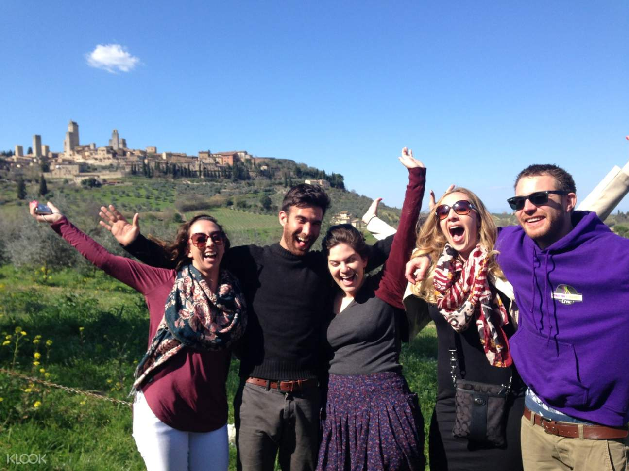 group of tourists posing with the tuscany medieval town in background
