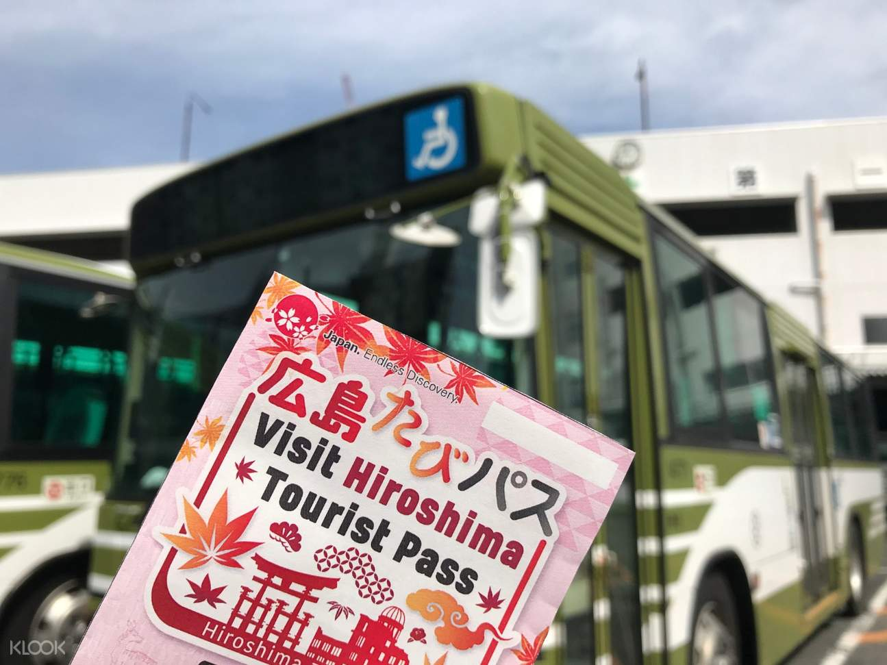 Hiroshima Tourist Pass being held up; there's a view of a bus