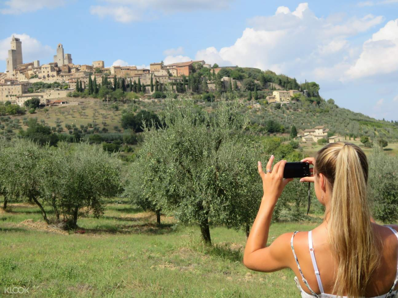 girl taking a photo of tuscany's medieval town