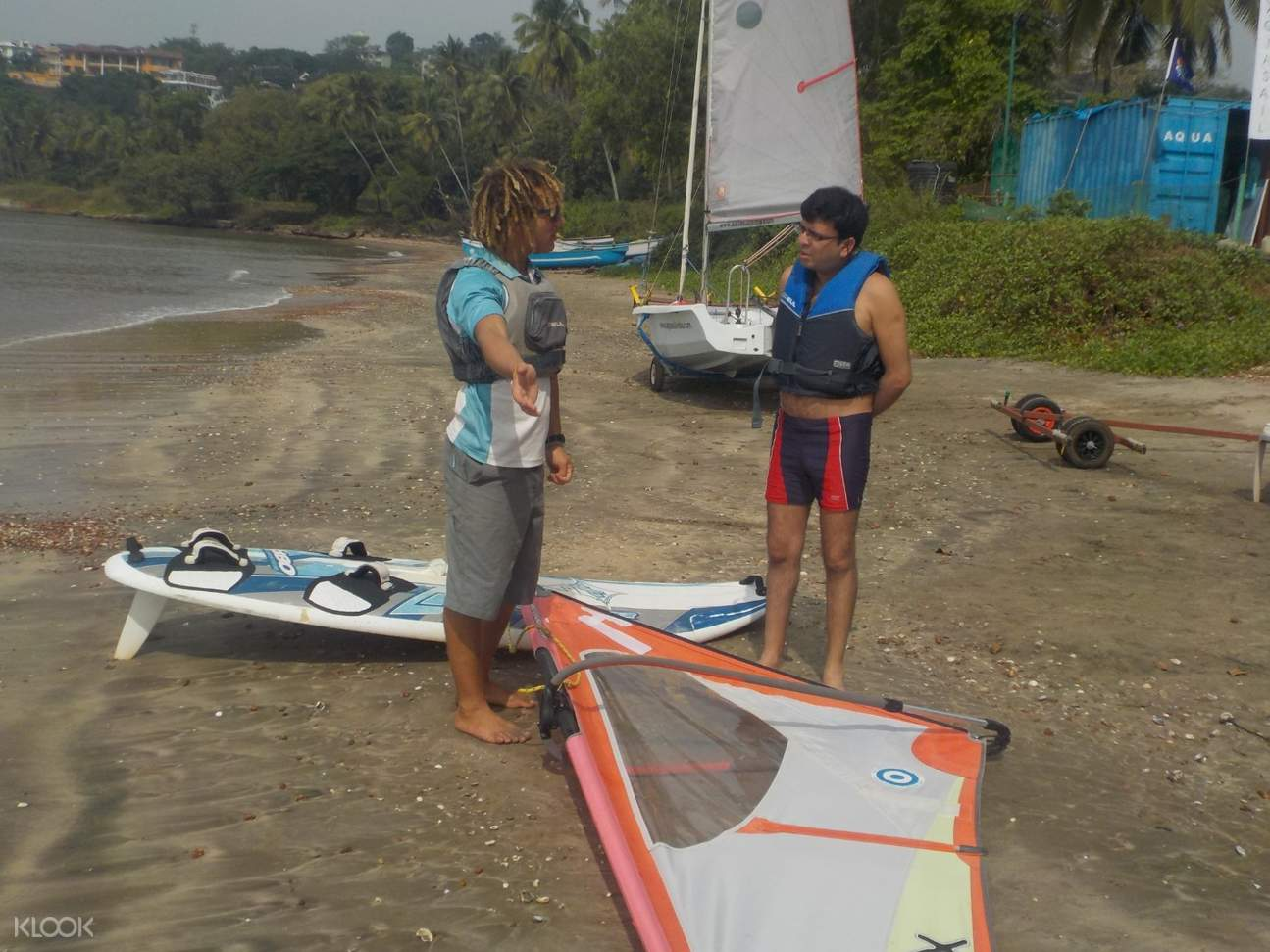 tourists learn windsurfing from instructor