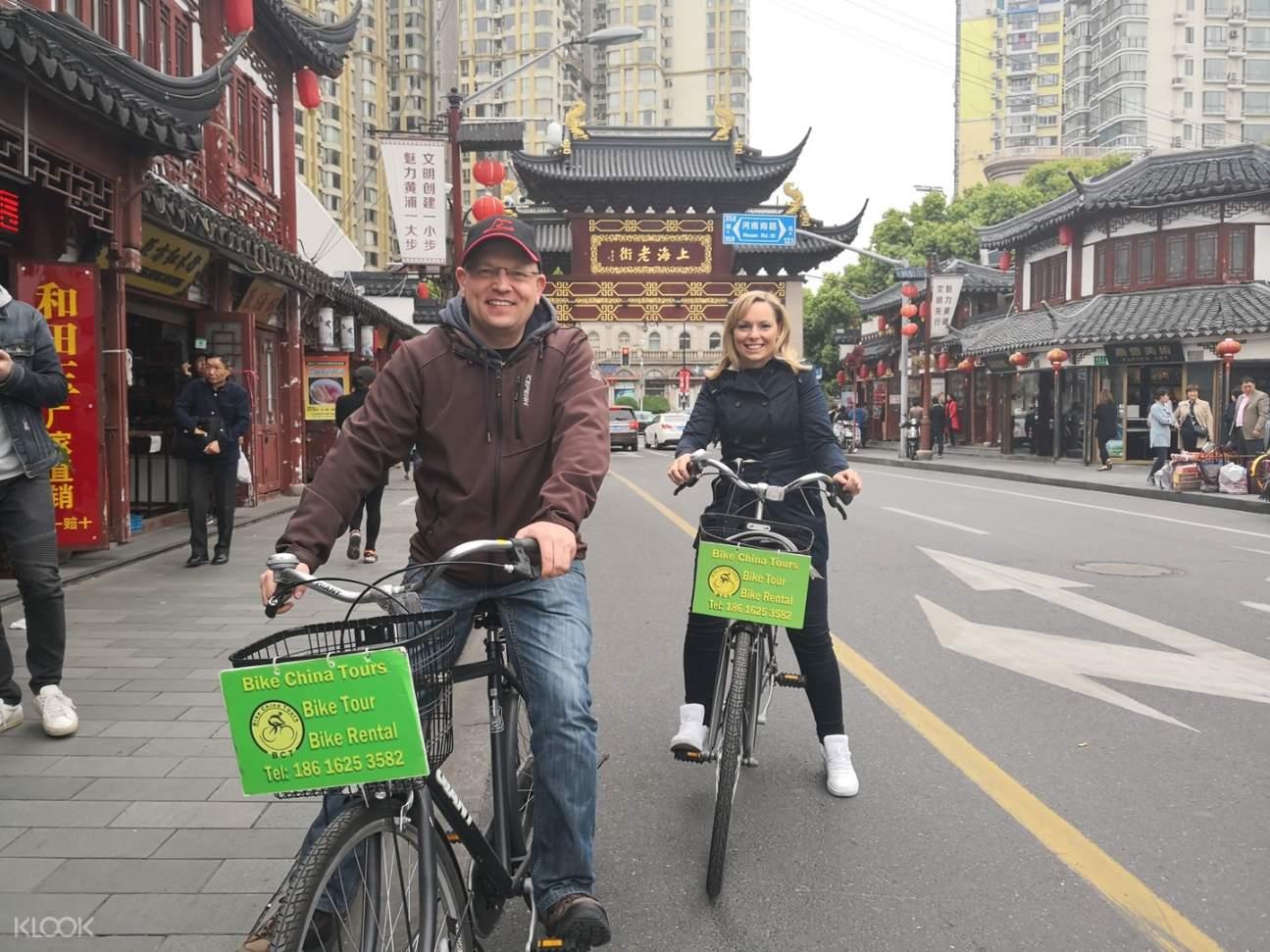 two people cycling through shanghai yu garden